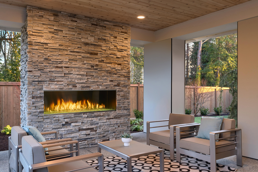Outdoor Lifestyles Lanai 60 linear gas fireplace by Majestic shown in a covered patio with yellow LED lights on